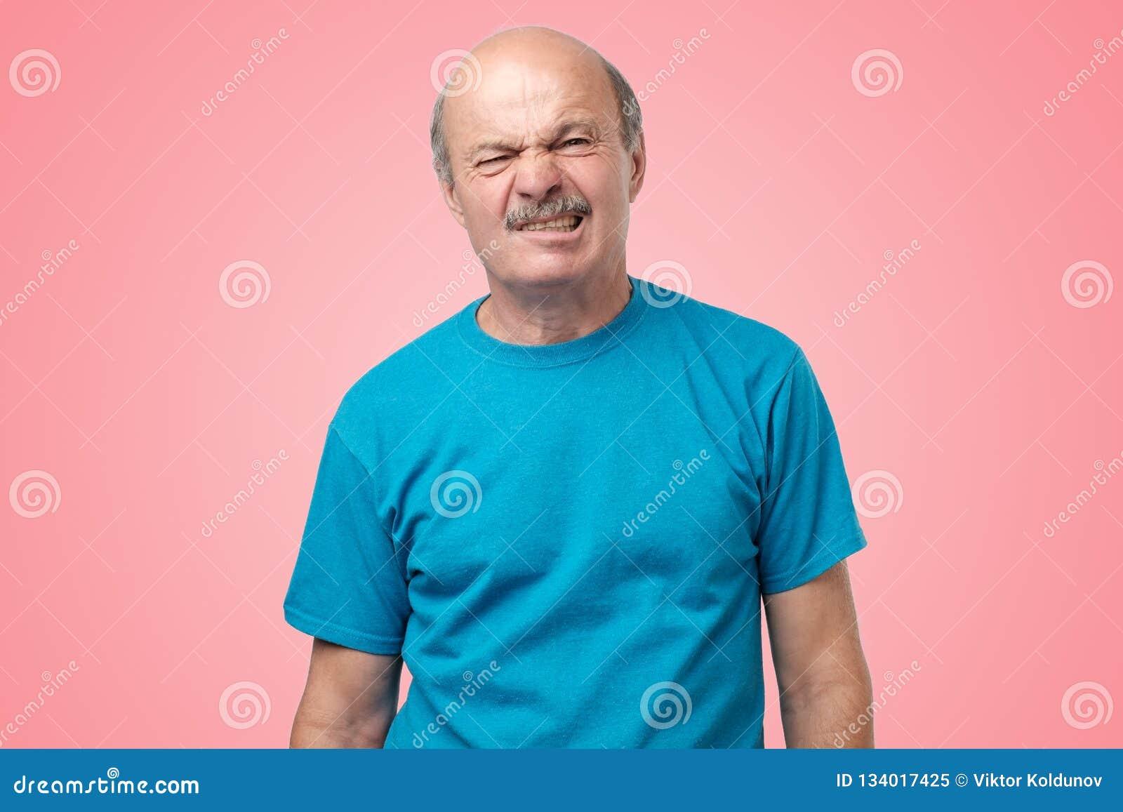 Adulto maturo in maglietta blu che ha un dubbio con repulsione sulla condizione del fronte sul fondo rosa