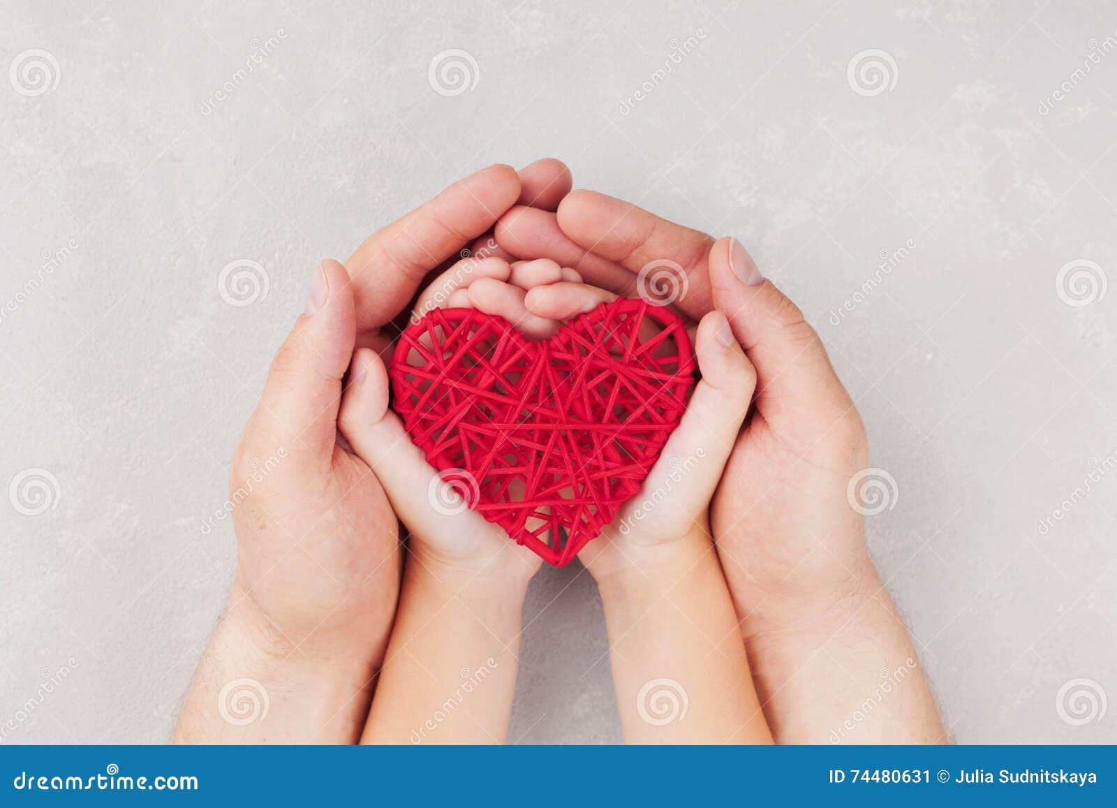 Adulto y niño que llevan a cabo el corazón rojo en la opinión superior de las manos Relaciones de familia, atención sanitaria, co