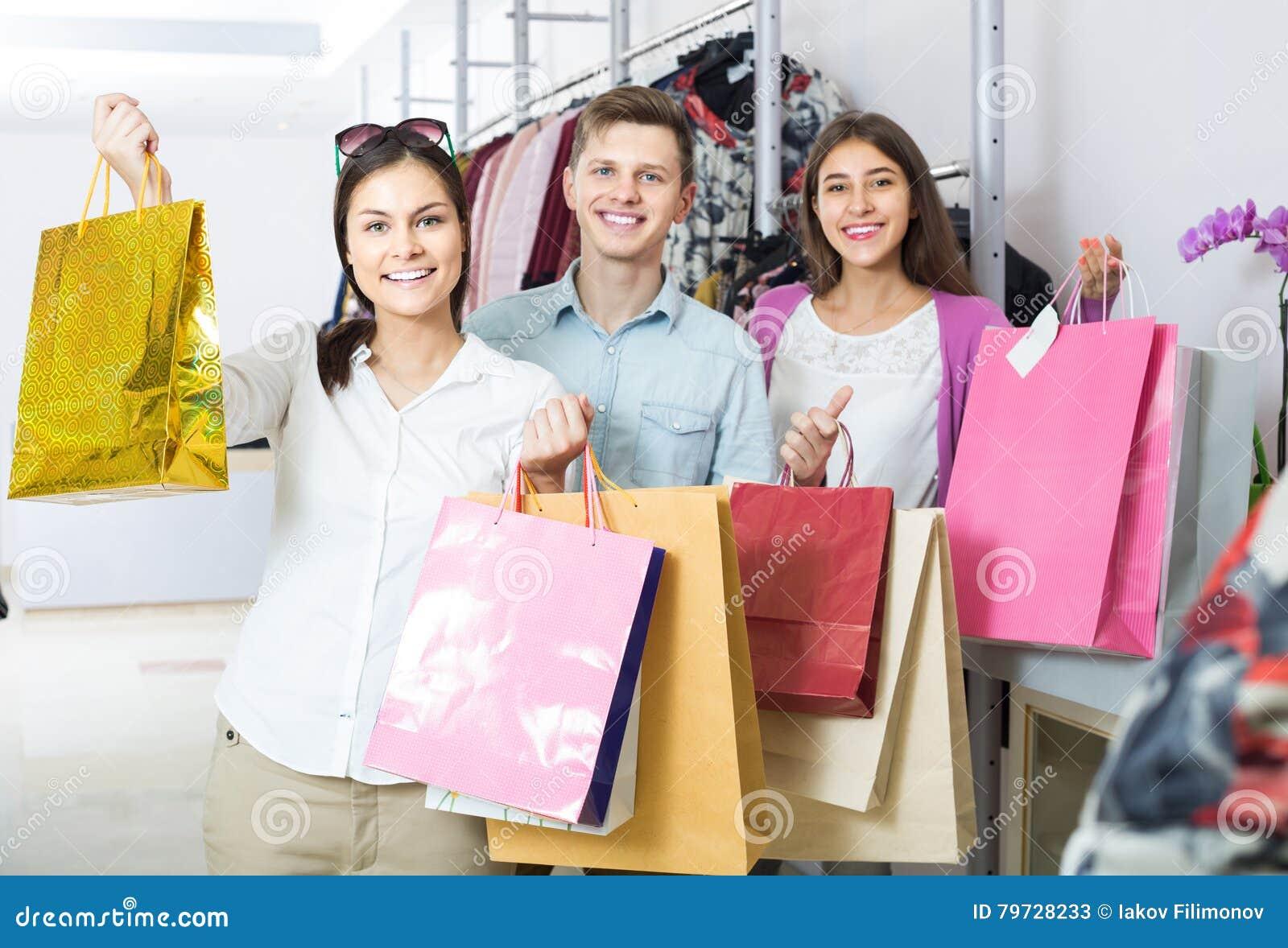 Adultos en el buen humor que celebra bolsos en la tienda de ropa