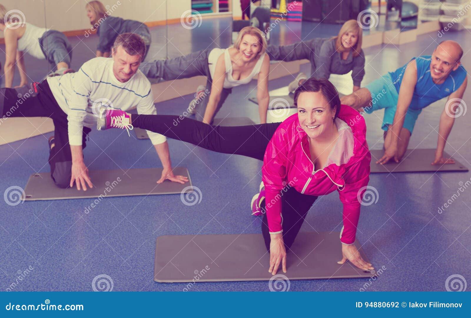 Adultos que hacen los pilates rutinarios