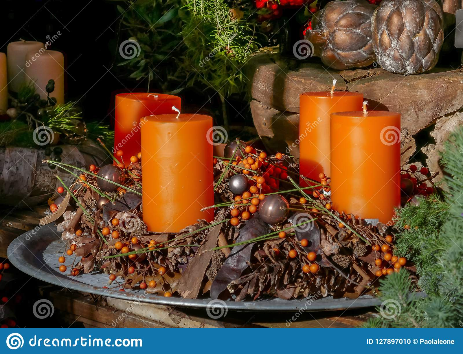 advent candles decoration with pine cones and leaves orange color and wooden elements
