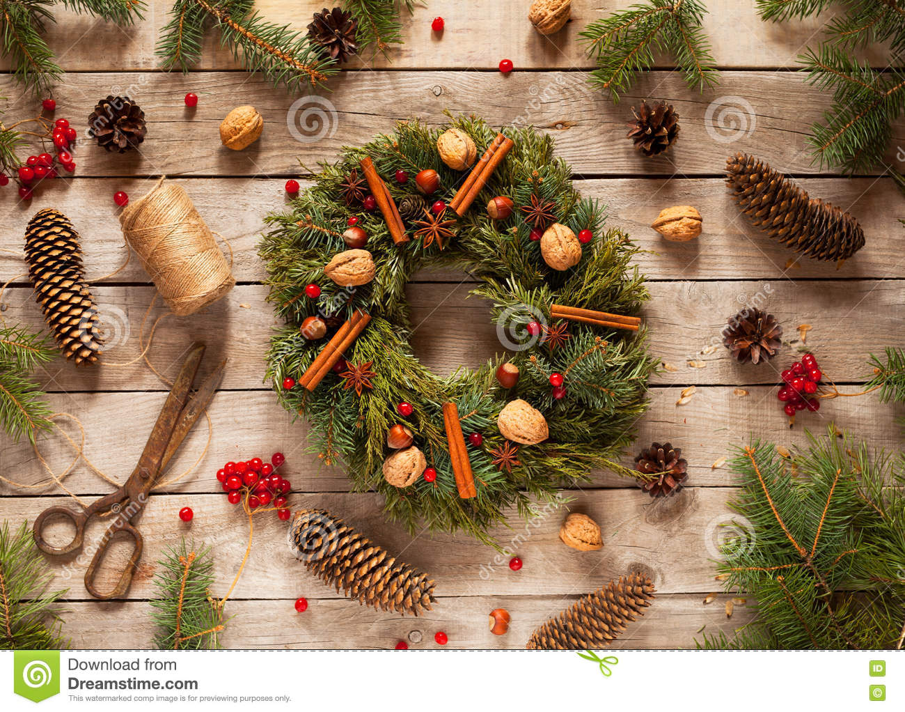 Advent Christmas wreath with natural decorations, pine cones spruce, nuts, candied fruit on wooden rustic background