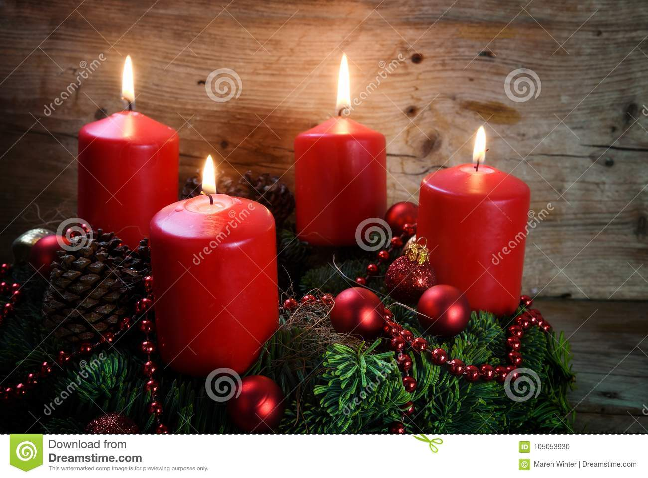 Advent wreath from fresh fir tree branches with four red burning