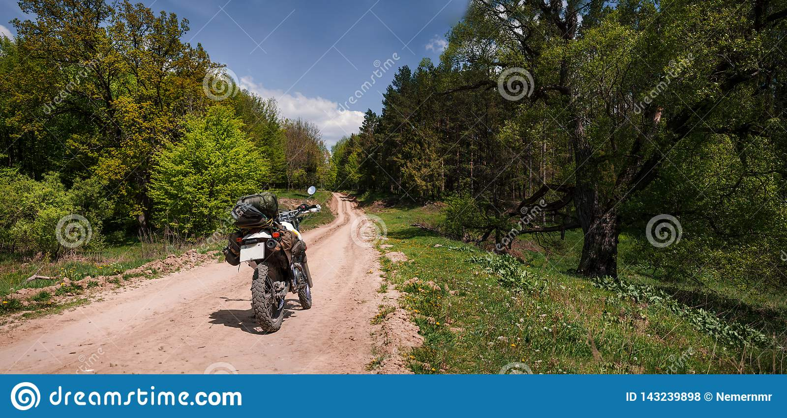Adventure motorcycle on dirt forest road, enduro, active lifestyle, travel lover concept