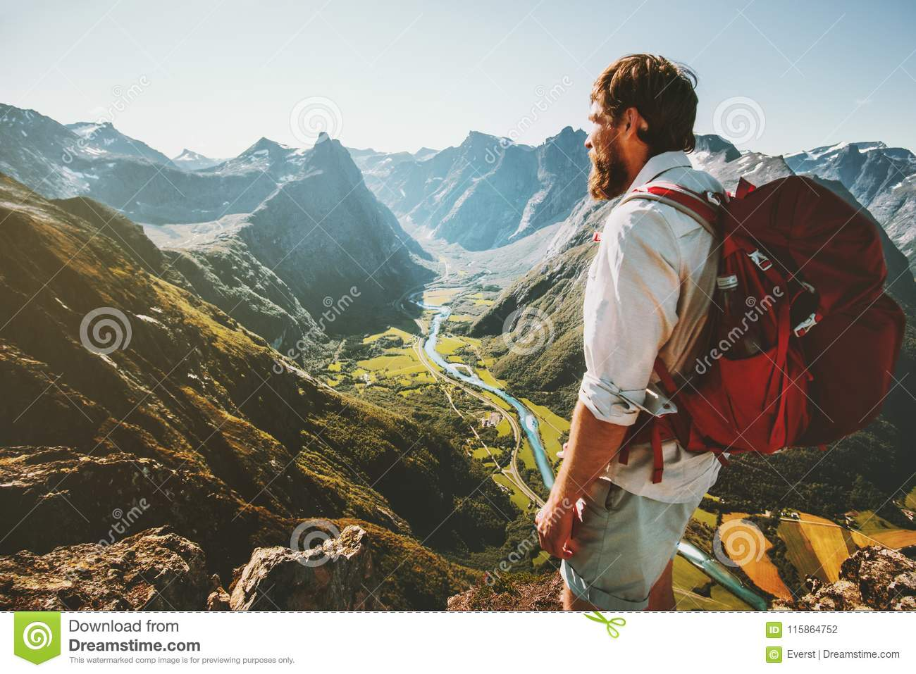 Adventure in mountains Man with red backpack alone on cliff