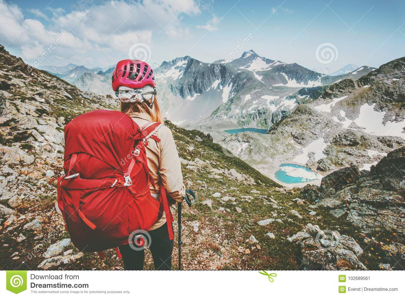 Adventurer tourist hiking in mountains with backpack Travel Lifestyle hiking adventure concept summer vacations outdoor exploring