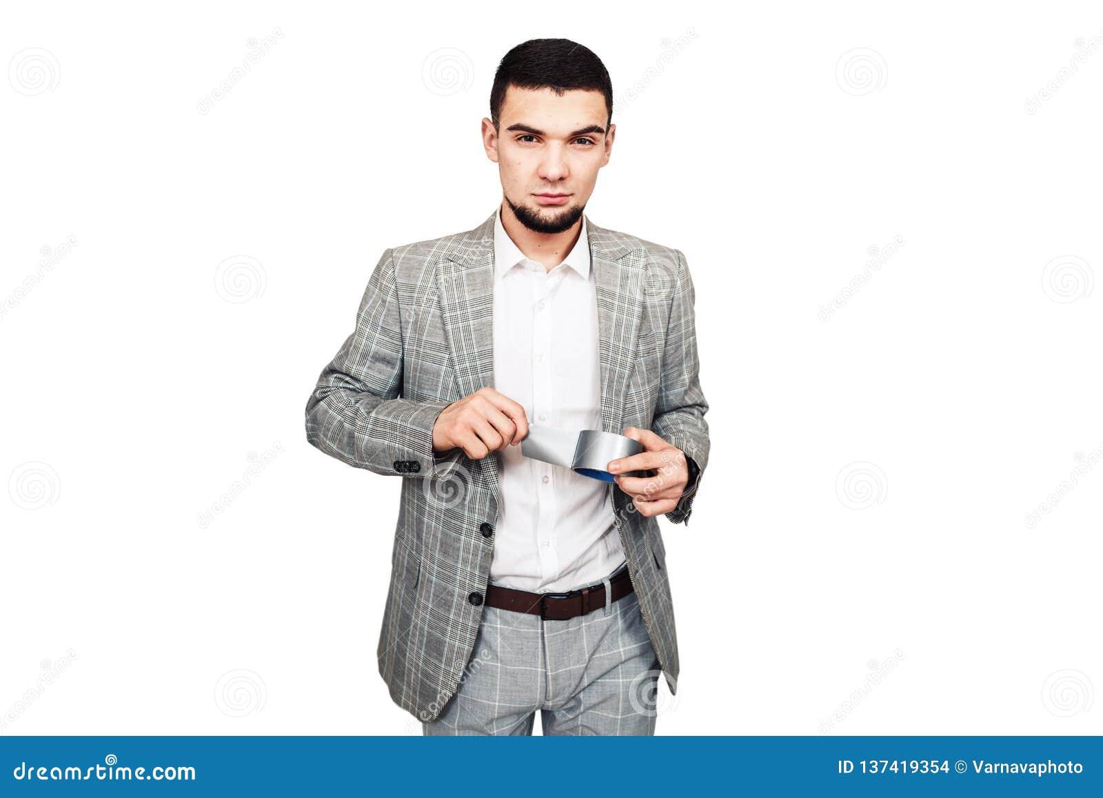 Adversaire de liberté de parole, dictateur Le jeune type barbu élégant dans un costume gris veut sceller votre bouche avec le rub