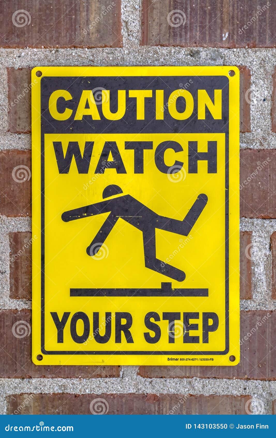 Advirta o relógio seu sinal da etapa em uma parede de tijolo