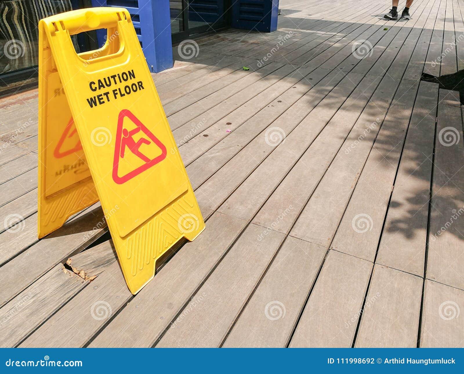 Advirta o sinal de aviso molhado do assoalho com borrado no assoalho de madeira