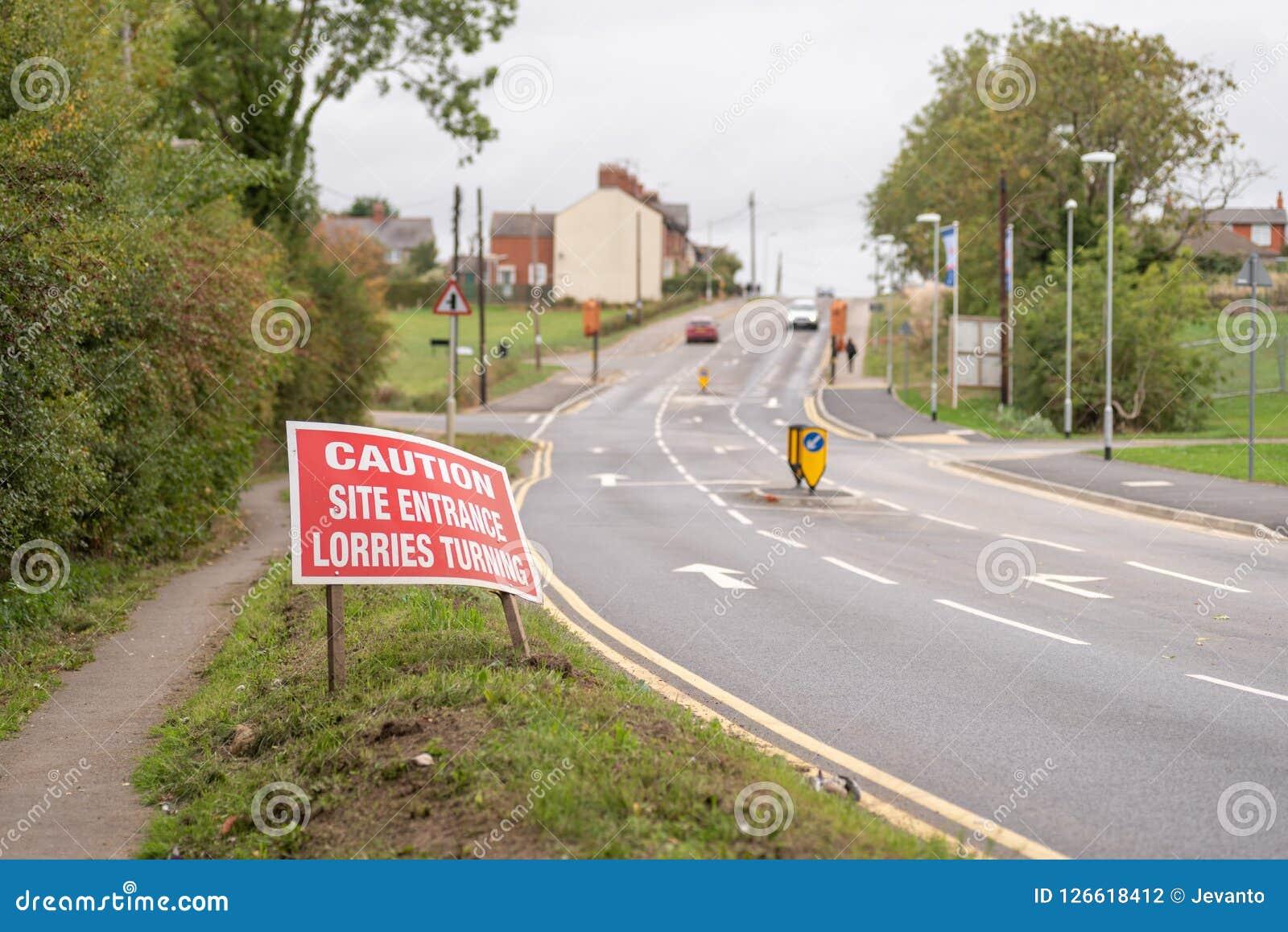 Advirta os caminhões da entrada do local que giram sinal de estrada de advertência na opinião britânica da luz do dia da estrada
