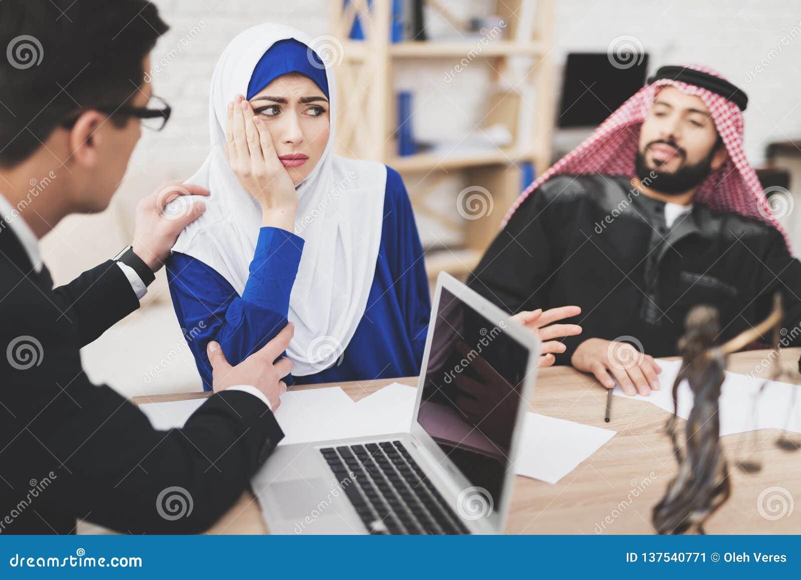 Advocaat in bureau met Arabische echtgenoot en vrouw De advocaat troost vrouw