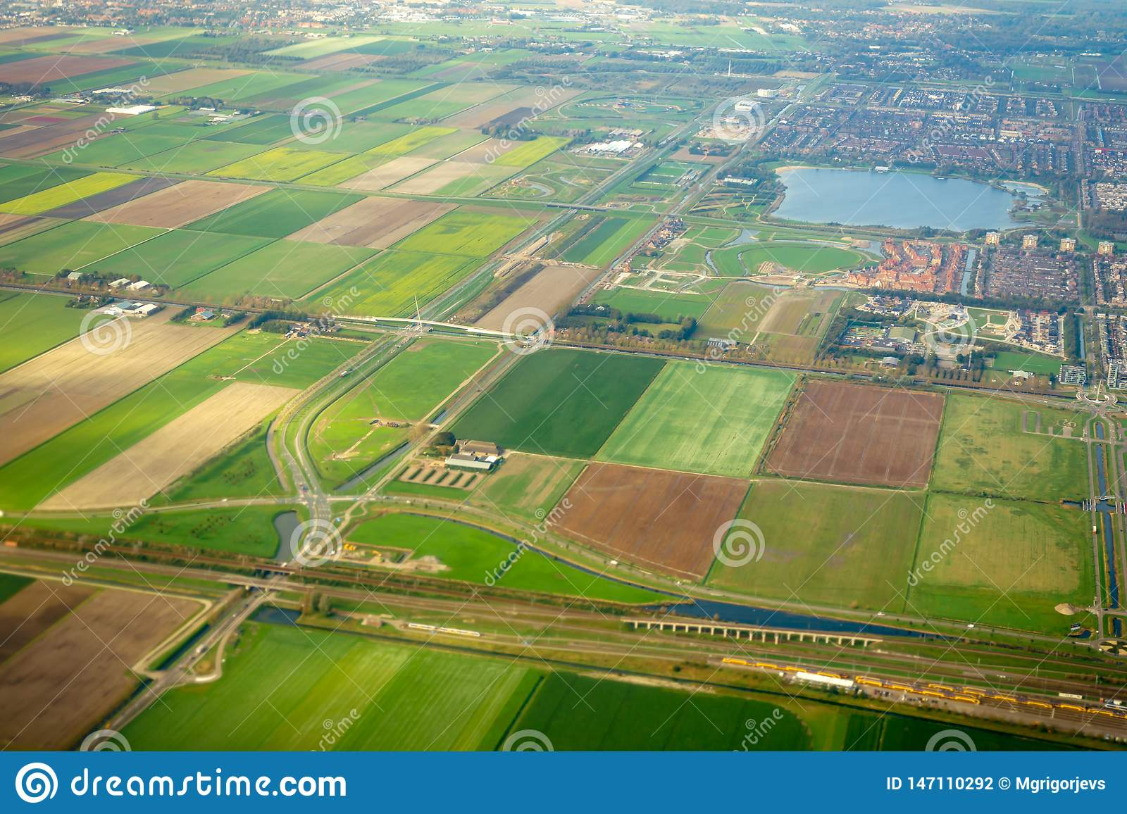Aeral view on agricultural fields and railway with train