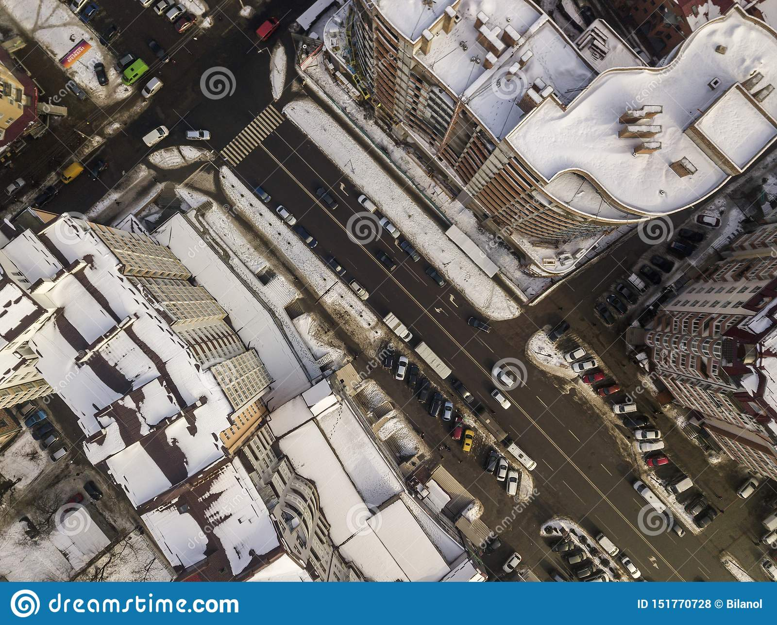 Aerial black and white winter top view of modern city with tall buildings, parked and moving cars along streets with road marking
