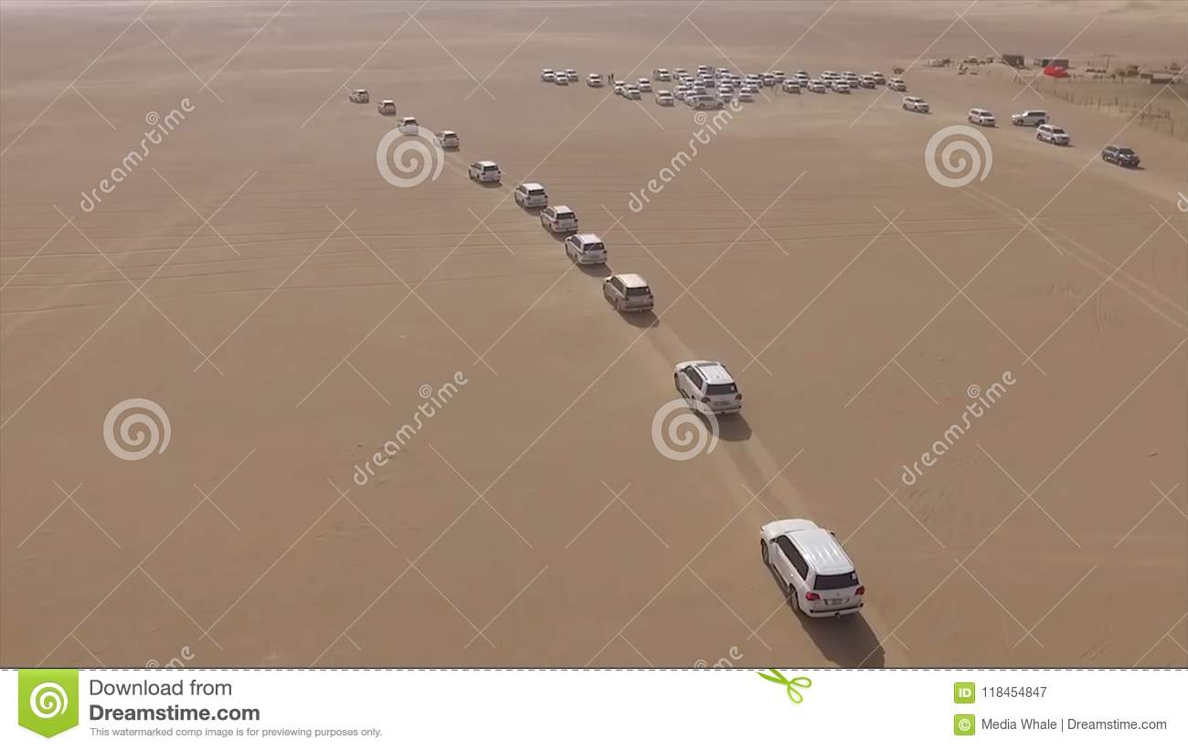 AERIAL: cars driving through desert. Stock. Aerial view of 4x4 off road land vehicle taking tourists on desert dune