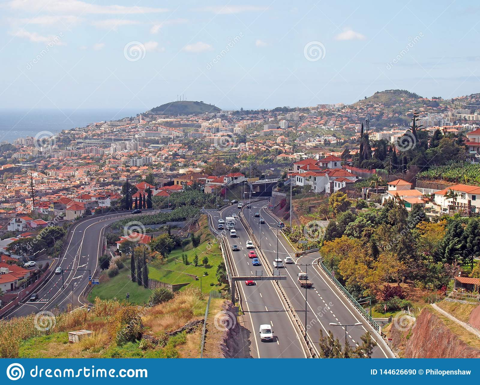 an aerial cityscape view of funchal showing traffic on the main VR1 motorway running into the city with the coast visible in the