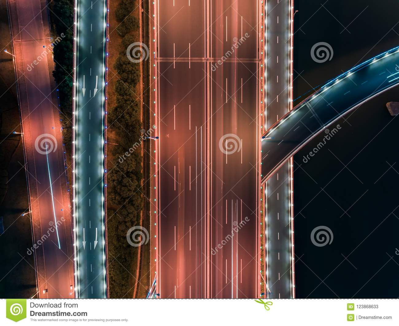 Aerial drone flight over night road traffic. Two-level road junction. Top view.