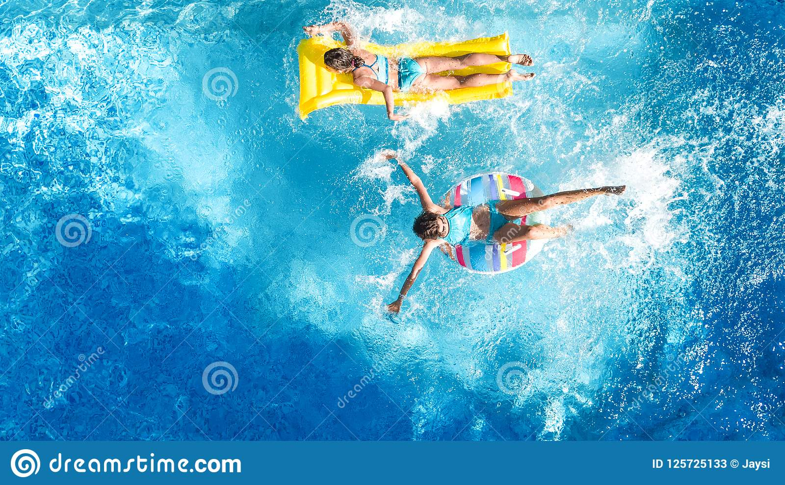 Aerial drone view of children in swimming pool from above, happy kids swim on inflatable ring donuts, girls have fun in water