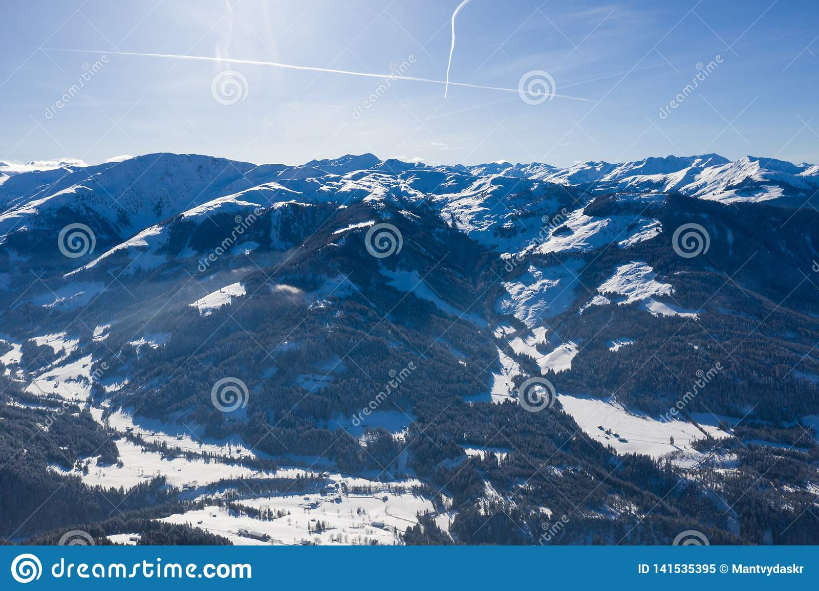 Aerial drone view of valley covered in snow in between mountains
