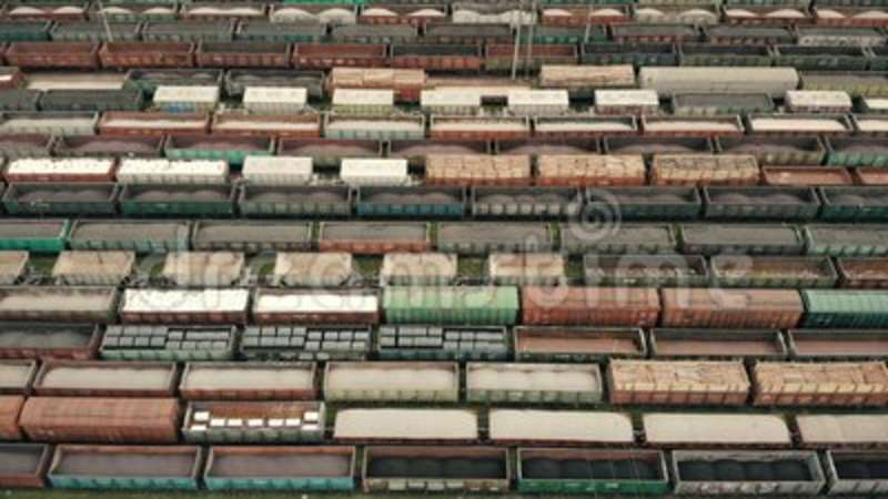 Aerial Flight over freight wagons. Colored freight wagons at the unloading and loading freight wagon station. Logistics.  stock video