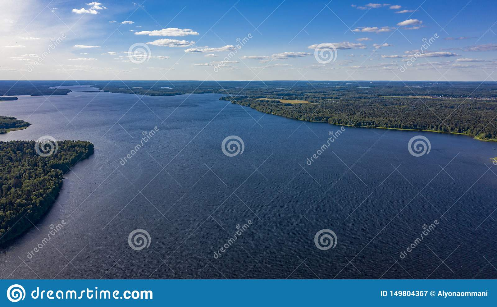 Aerial photo of the big lake in the forest with cumulus clouds