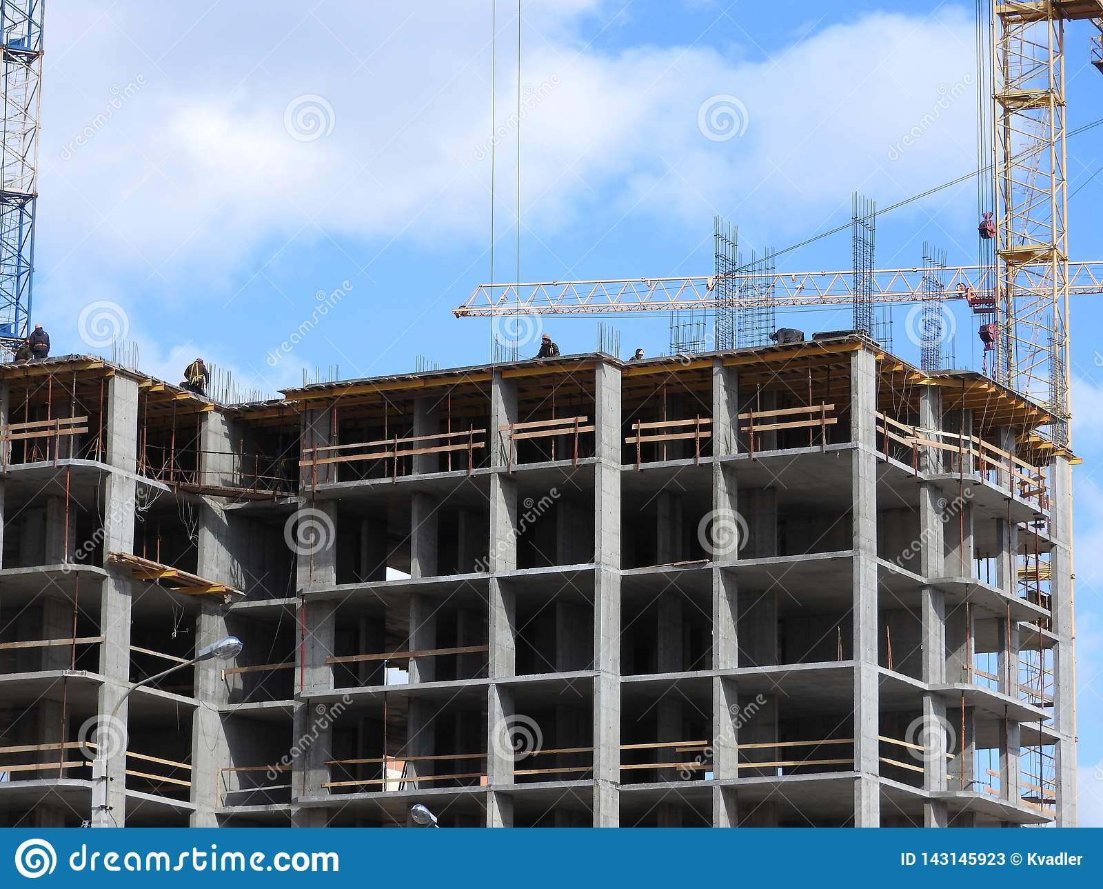 Aerial photograph of an unrecognized civil engineer without a face, watching the work of roof builders on the construction site.