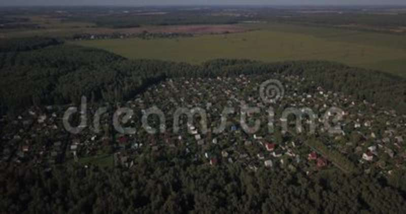 AERIAL SHOT: Beautiful small village or township 4k 4096 x 2160 pixels. AERIAL SHOT: Beautiful small village or township in the summer forest. A lot of houses stock video footage