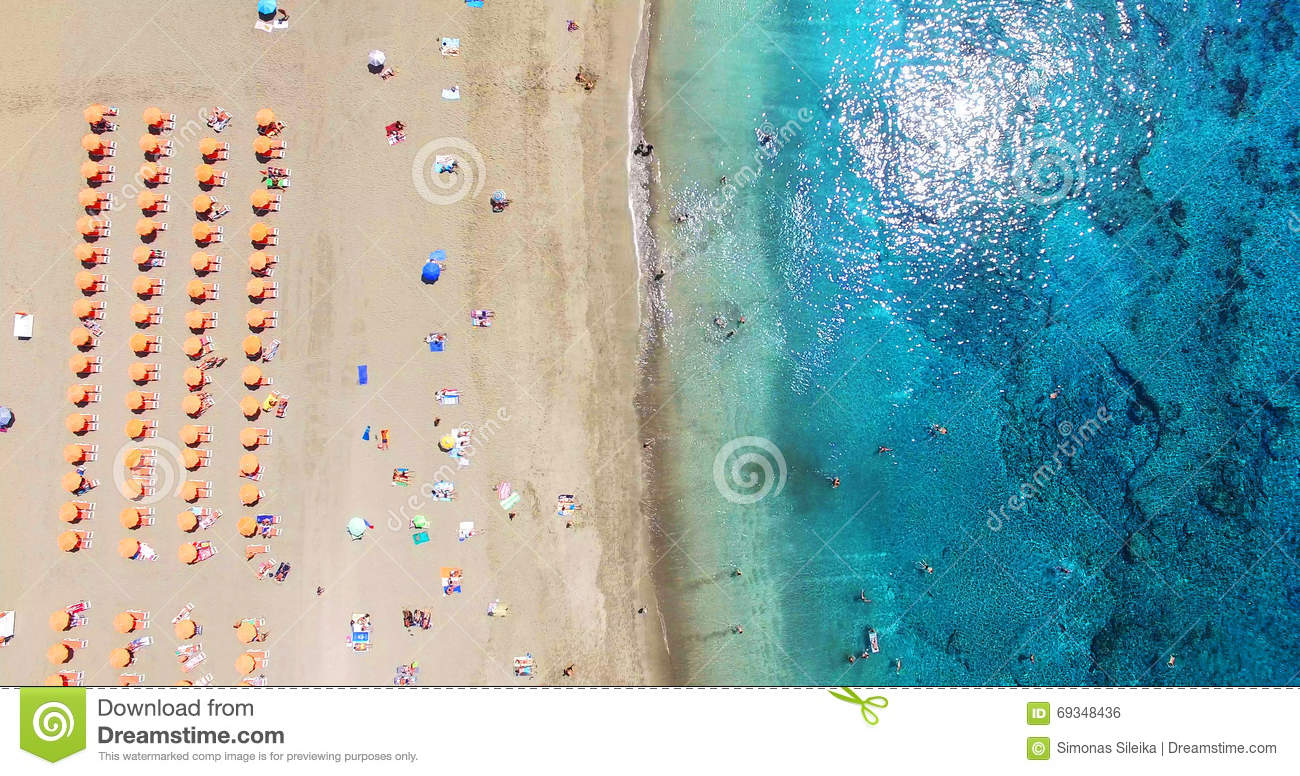 AERIAL. Summer beach with people and turquoise ocean water