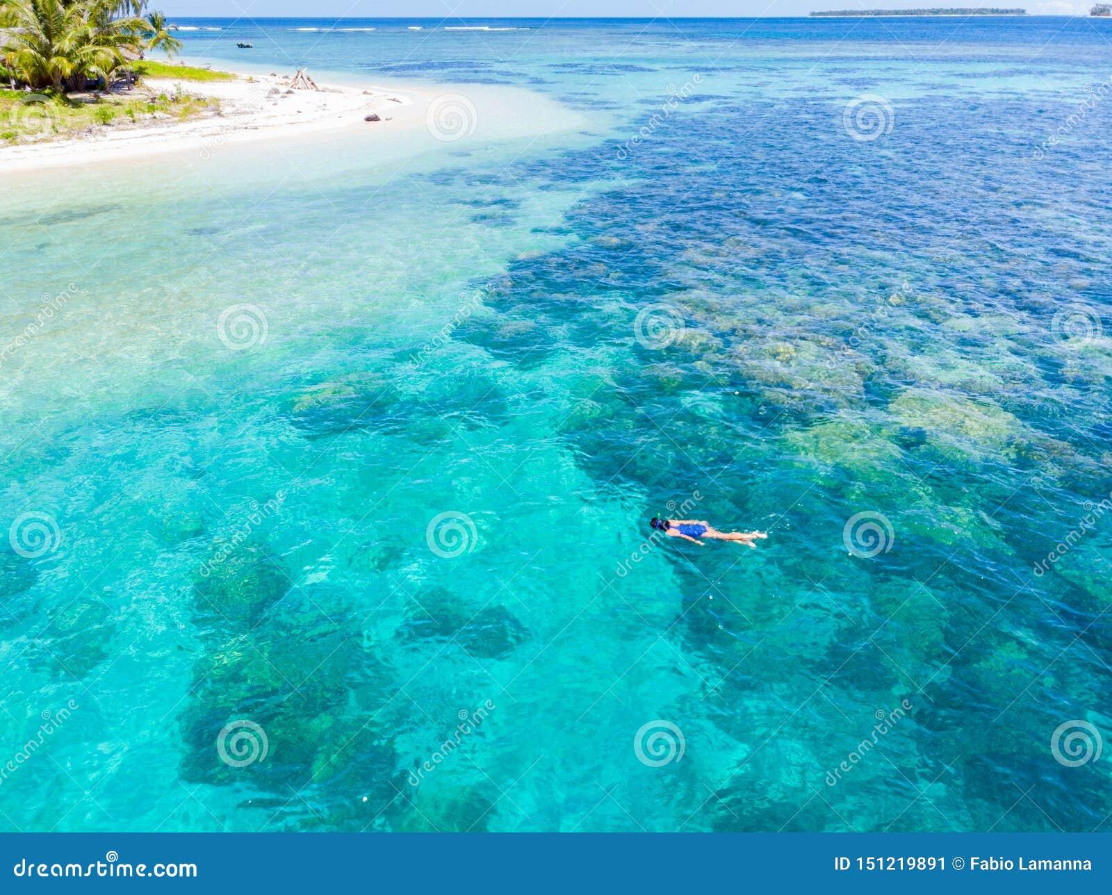 Aerial top down people snorkeling on coral reef tropical caribbean sea, turquoise blue water. Indonesia Banyak Islands Sumatra,
