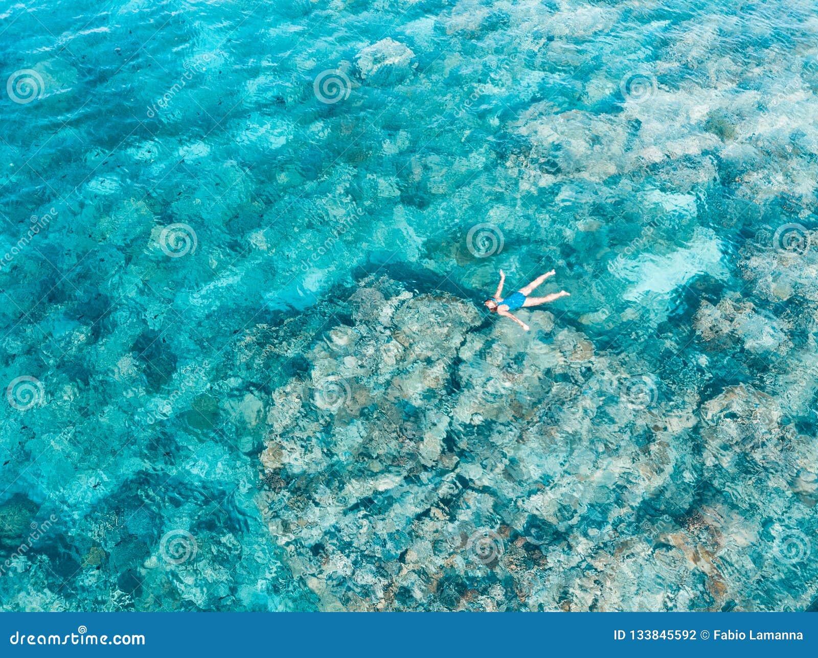 Aerial top down people snorkeling on coral reef tropical caribbean sea, turquoise blue water. Indonesia Wakatobi archipelago,