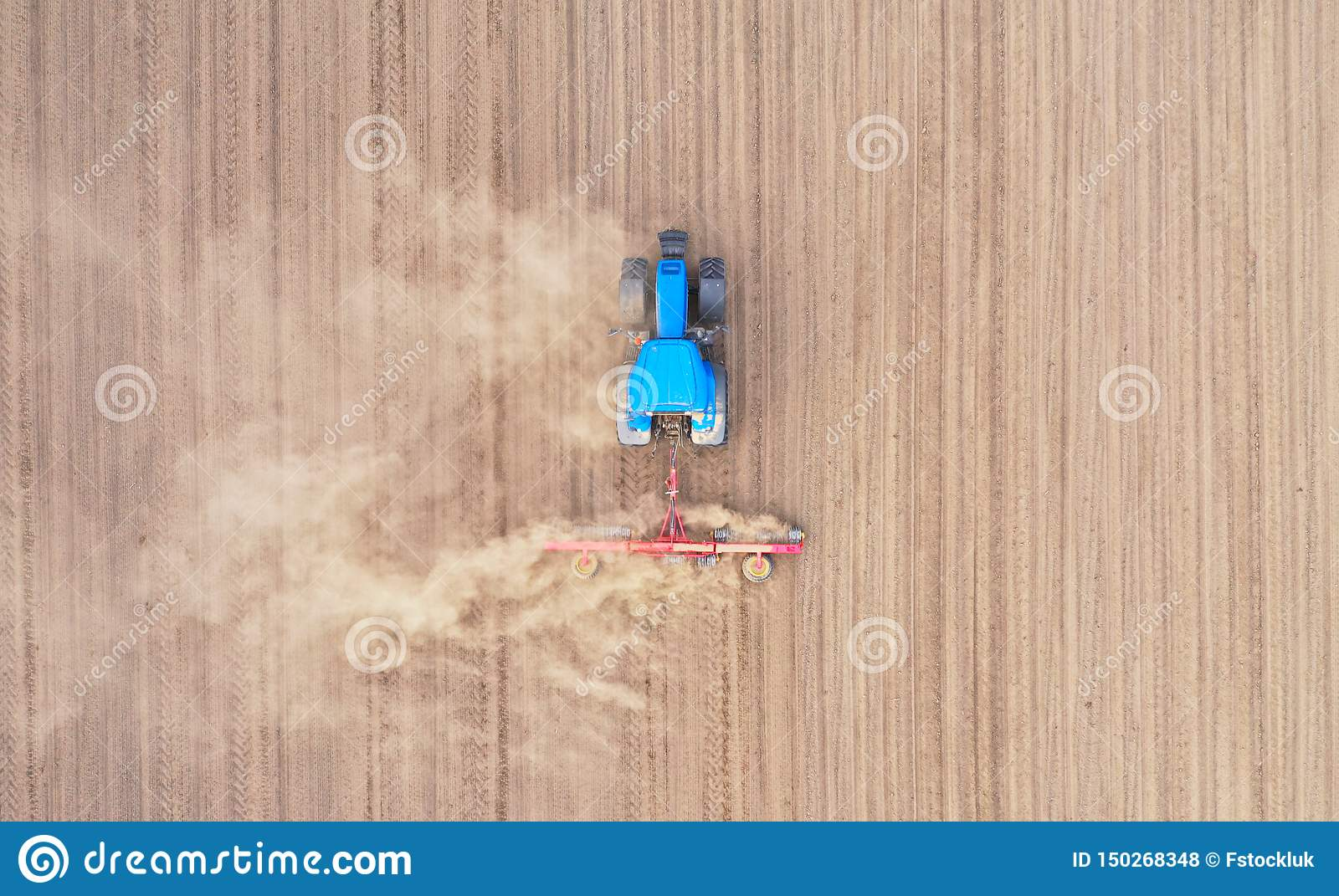Aerial Top Down View On Blue Tractor Pulling A Plow