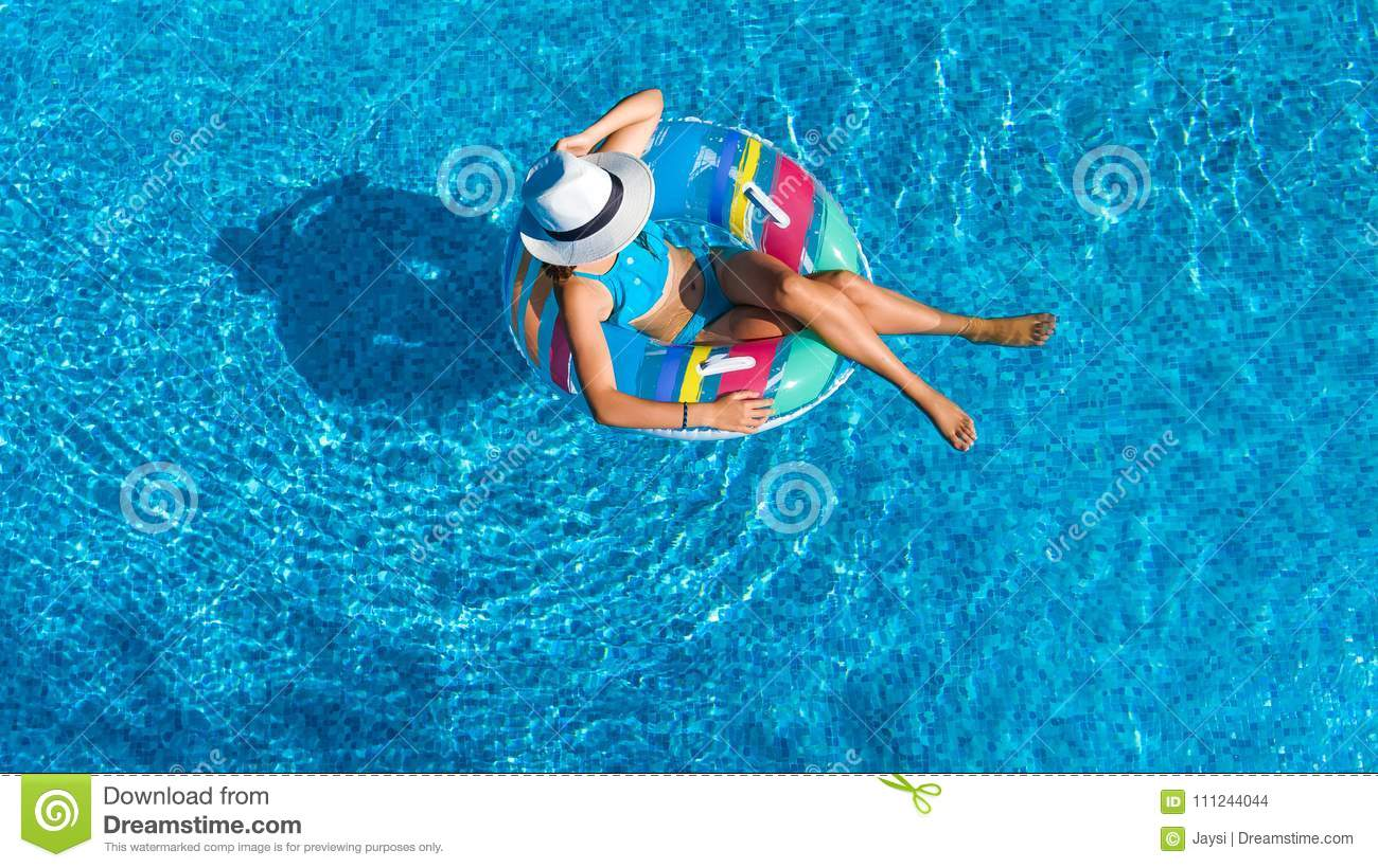 Aerial top view of beautiful girl in swimming pool from above, relax swim on inflatable ring donut and has fun in water