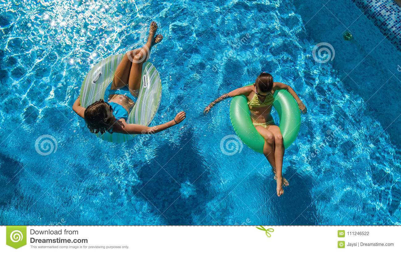 Aerial top view of children in swimming pool from above, happy kids swim on inflatable ring donuts and have fun in water