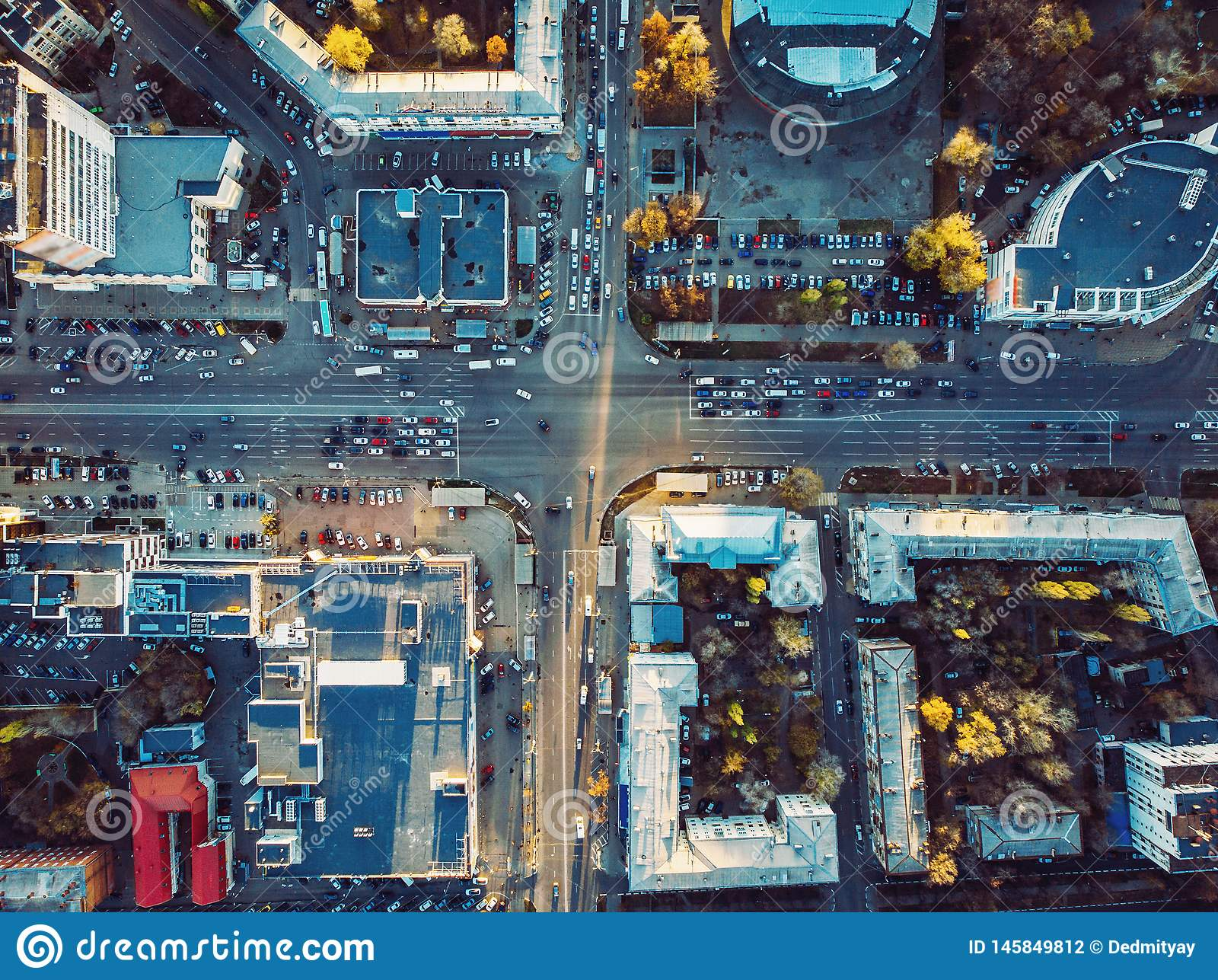 Aerial top view of city asphalt roads with lot of vehicles or car traffic and buildings, modern urban intersections and junctions