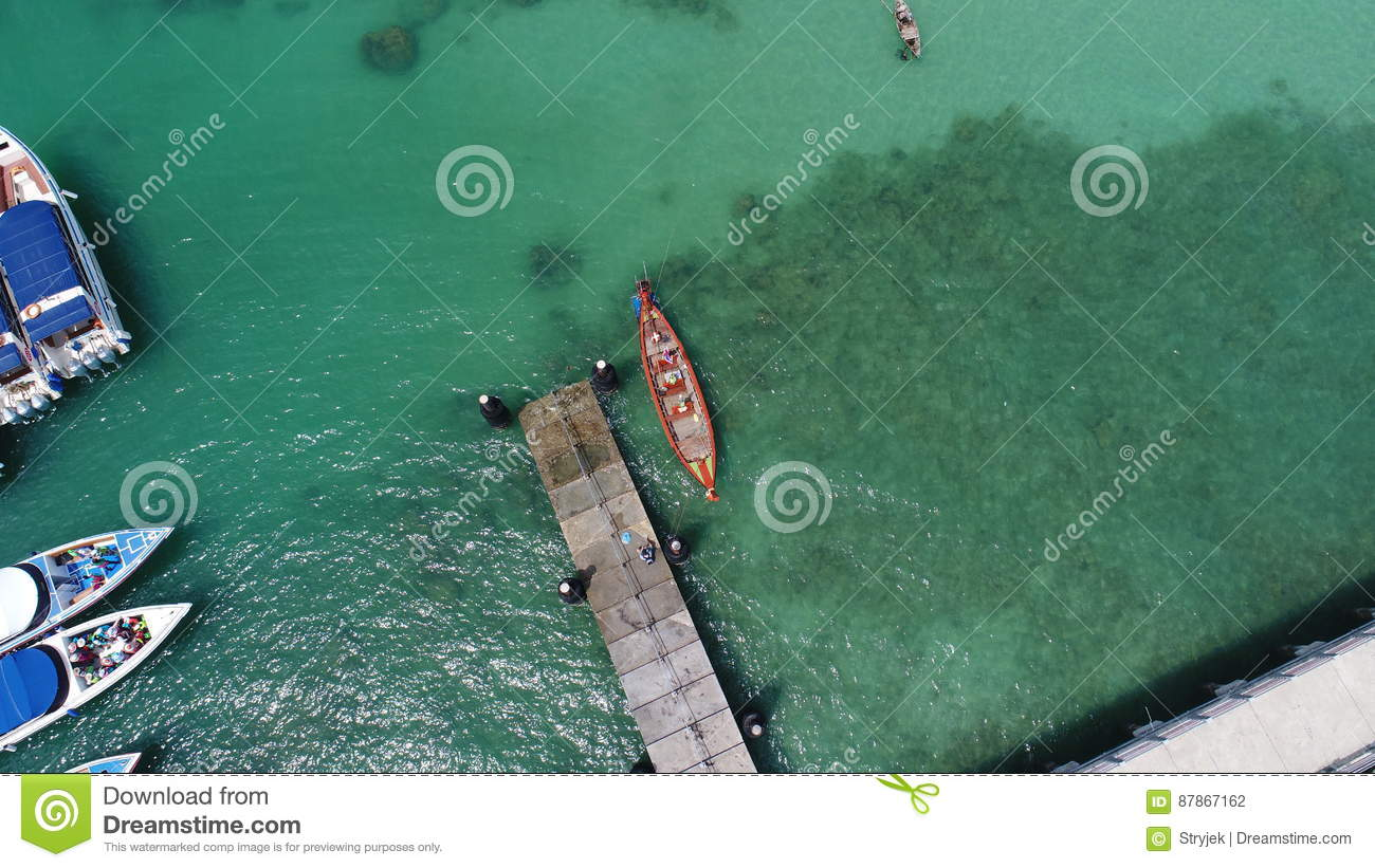 Aerial top view drone photo of floating boat on water surface and pier on Rawai beach in Phuket