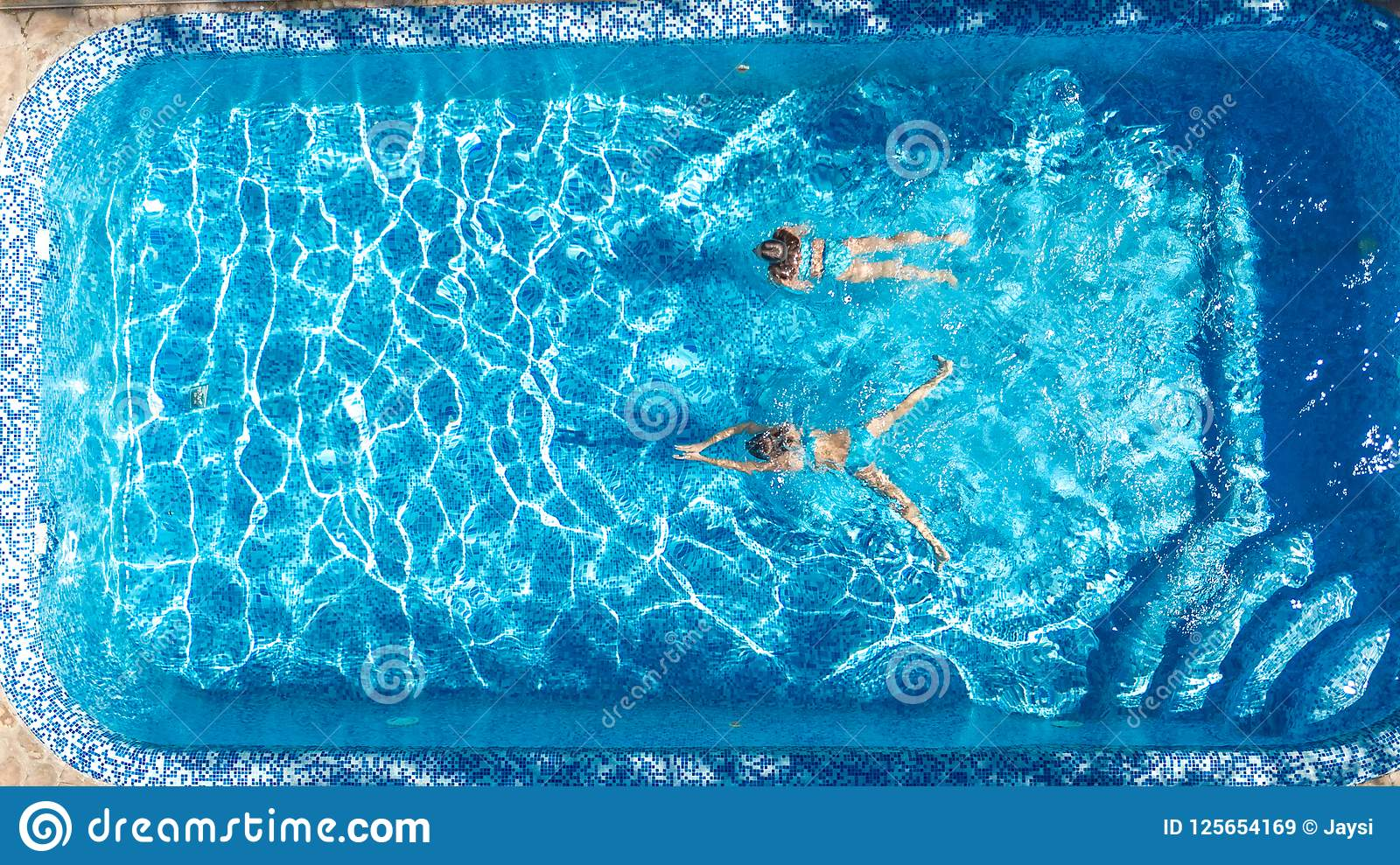 Aerial top view of girls in swimming pool water from above - Swimming pool girl christmas vacation ...