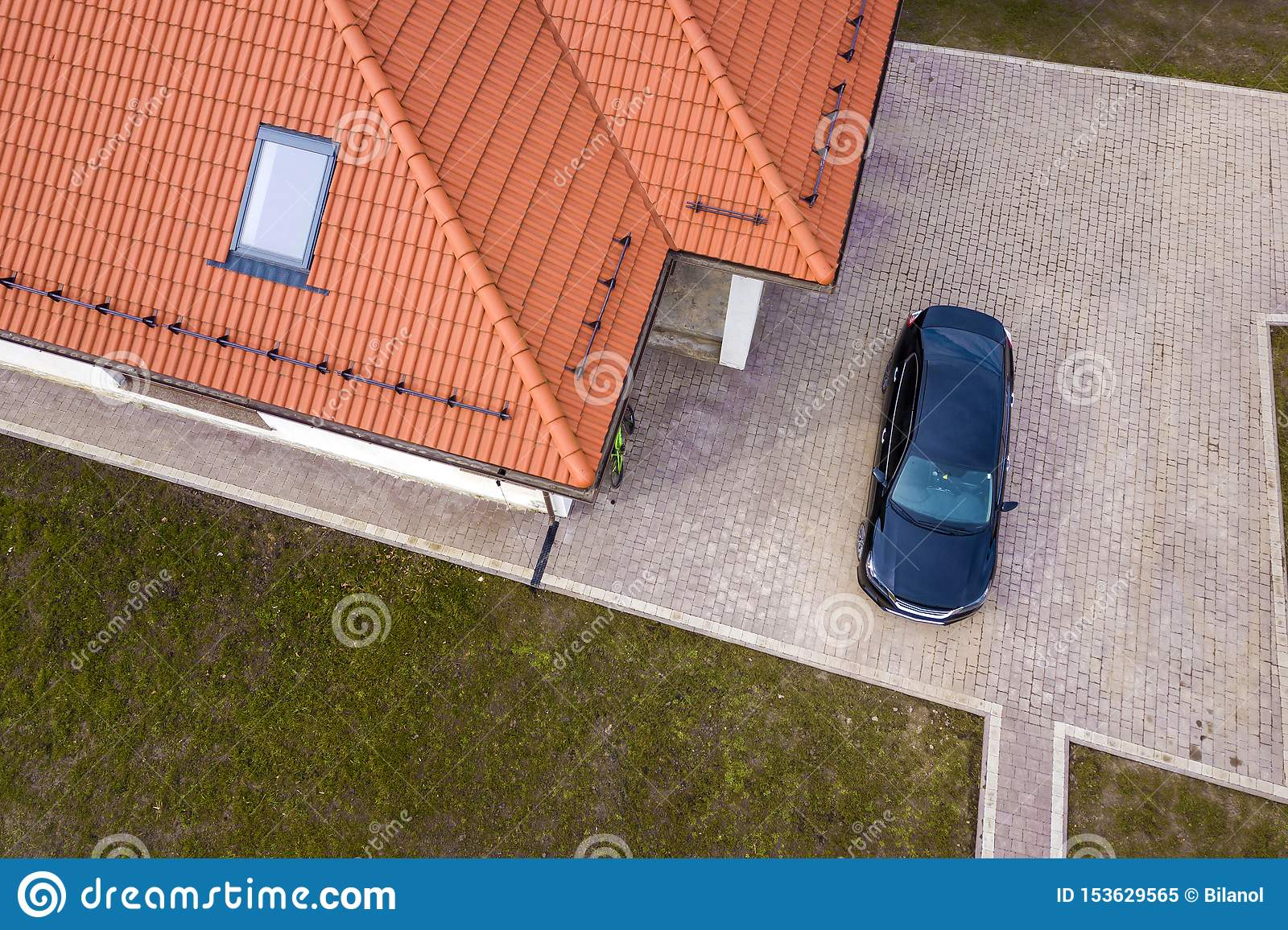 Aerial top view of house metal shingle roof with attic window and black car on paved yard