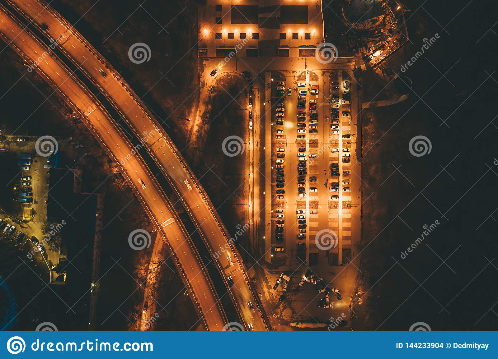 Aerial top view of illuminated city car parking with vehicles at night near motorway with traffic