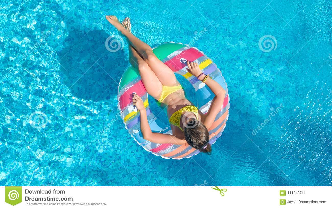 Aerial top view of little girl in swimming pool from above, kid swims on inflatable ring donut , child has fun in water