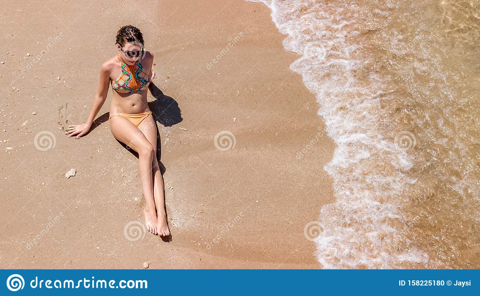 Aerial top view of young woman in bikini relaxing on sand tropical beach by sea and waves from above, girl on tropical island