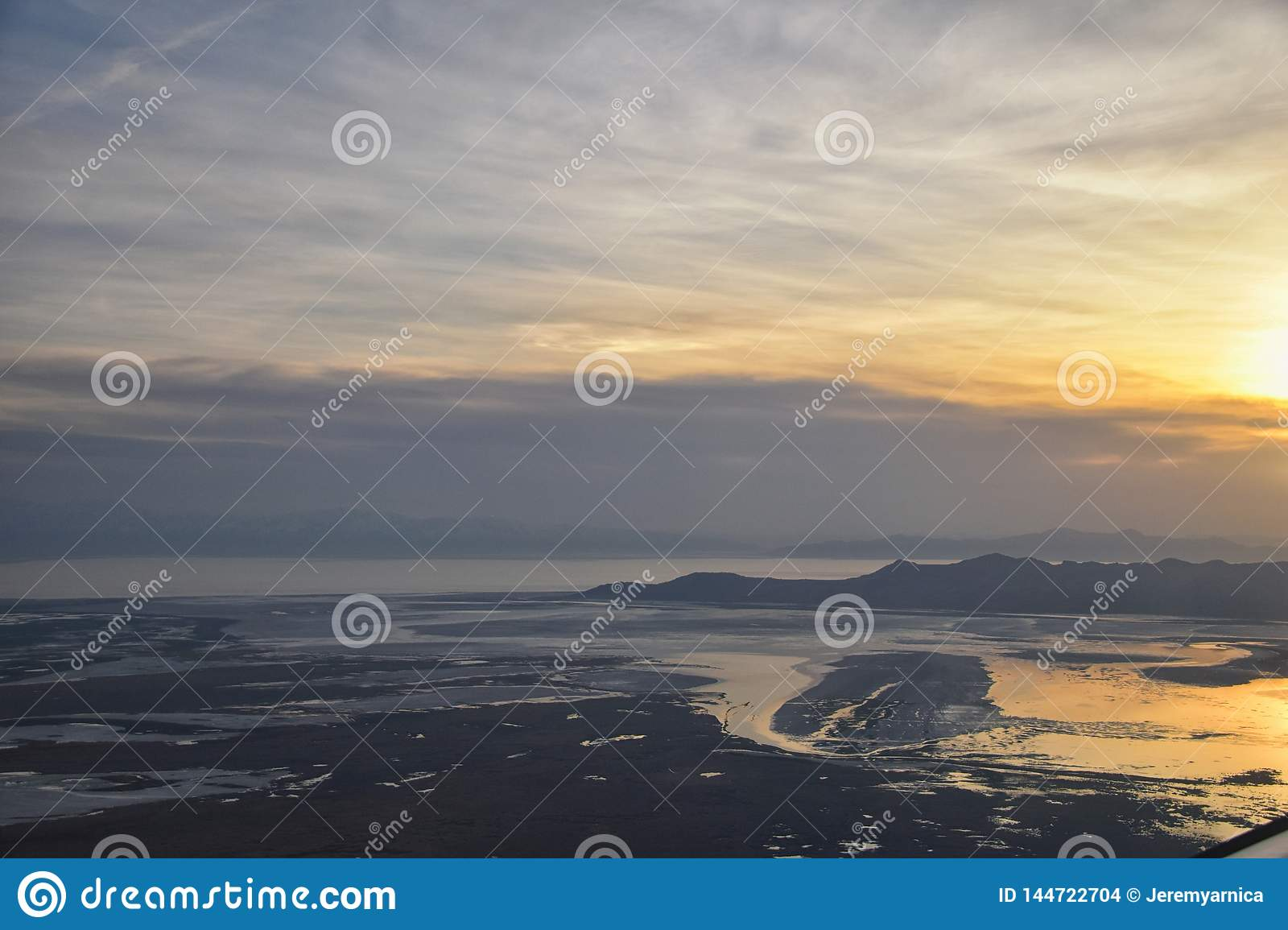 Aerial view from airplane of Antelope Island at sunset, view from Magna, sweeping cloudscape at sunrise with the Great Salt Lake
