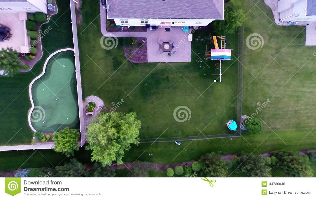 aerial view of backyard putting green from in air flight above
