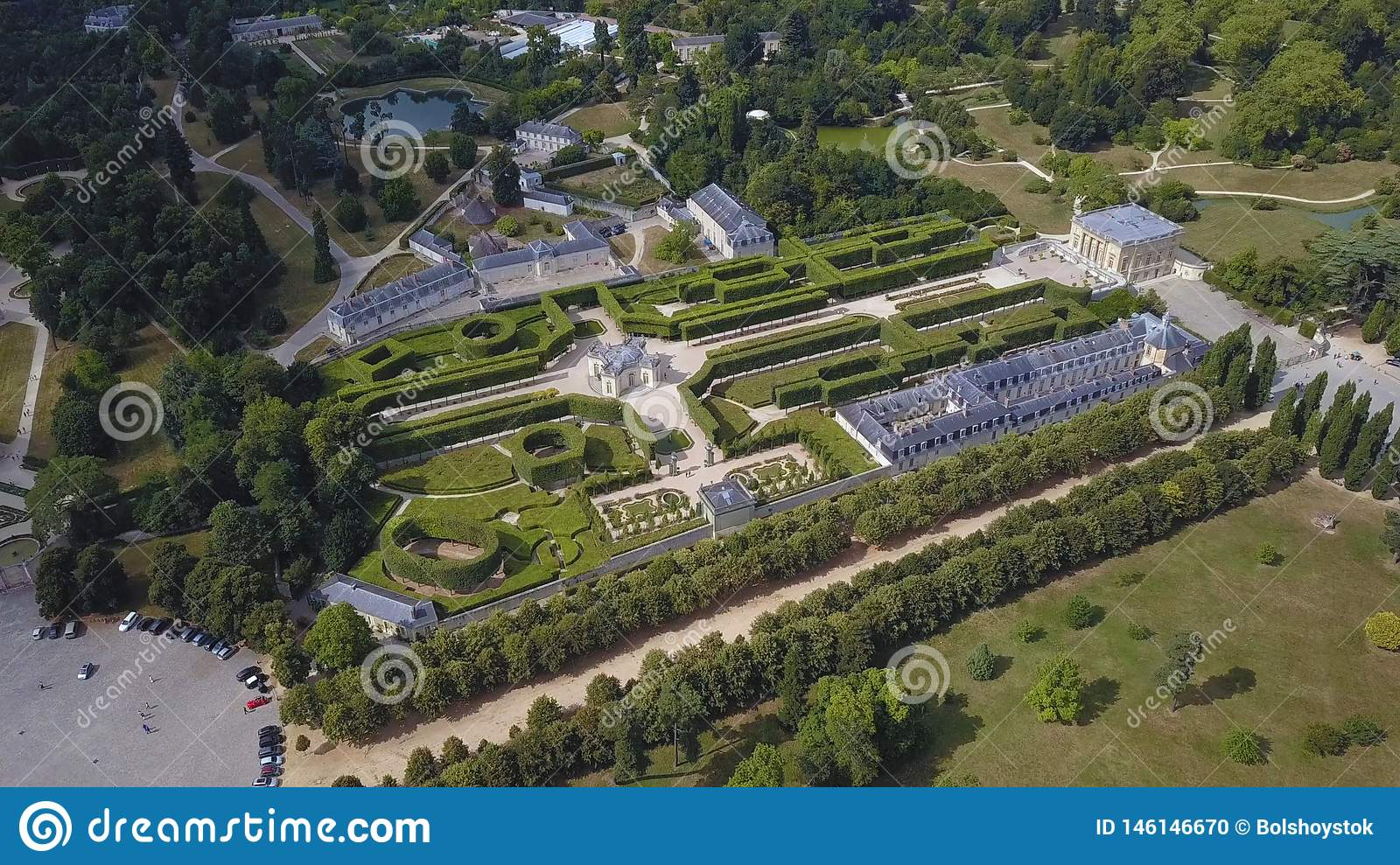 Aerial view of beautiful light palace and other buildings in architectural complex with picturesque French garden