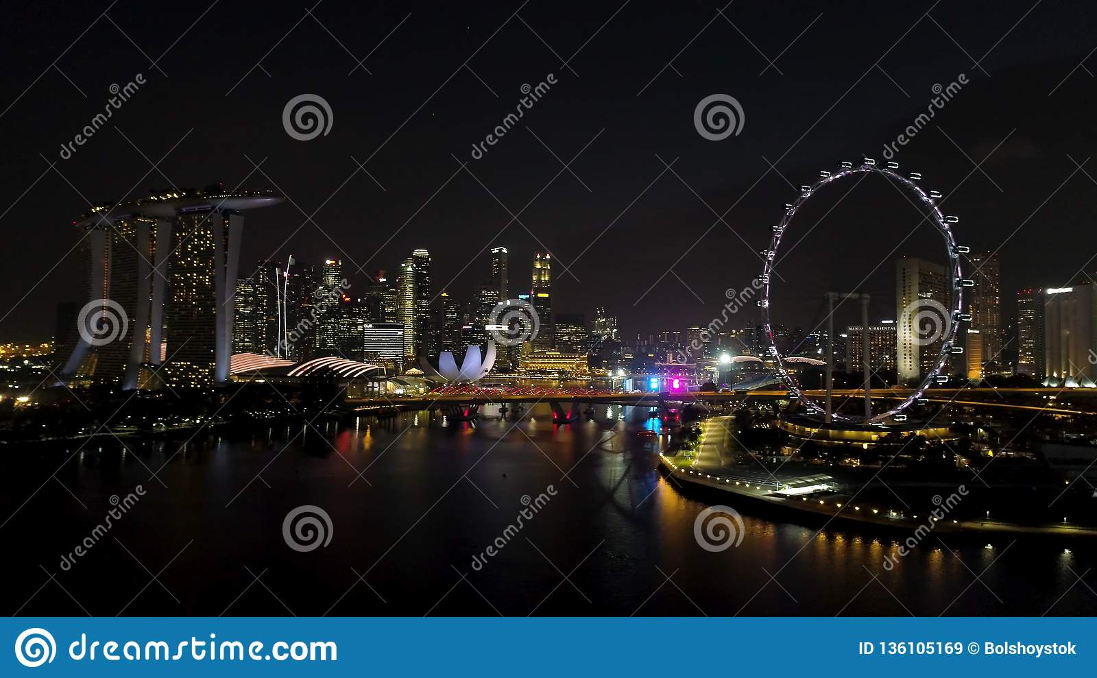 Singapore - 25 September 2018: Aerial view of big city with many lights, cloudy sky, and ferris wheel at night. Shot
