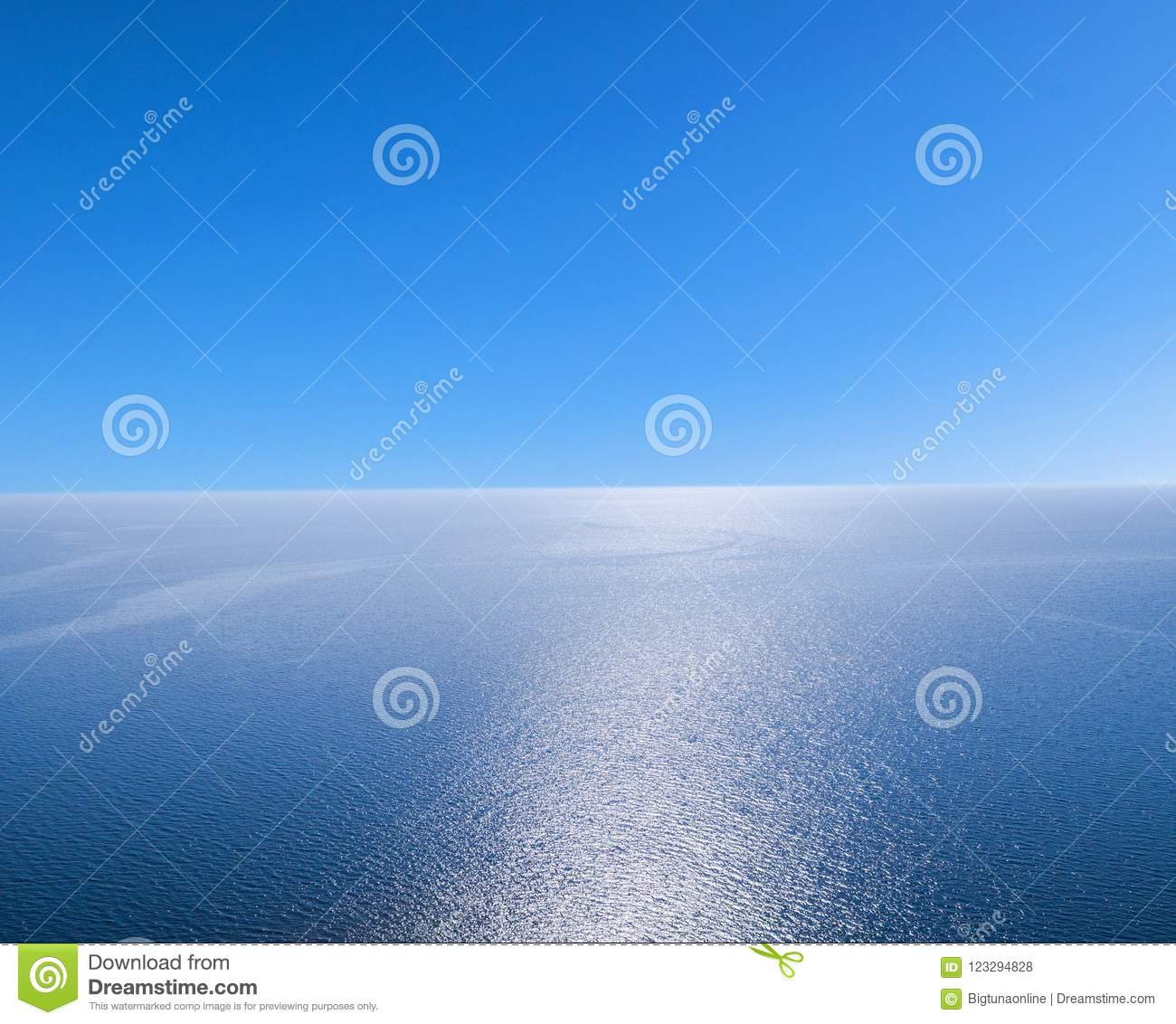 Aerial view of a blue sea water background and sun reflections. Aerial flying drone view. Waves water surface texture on sunny tro