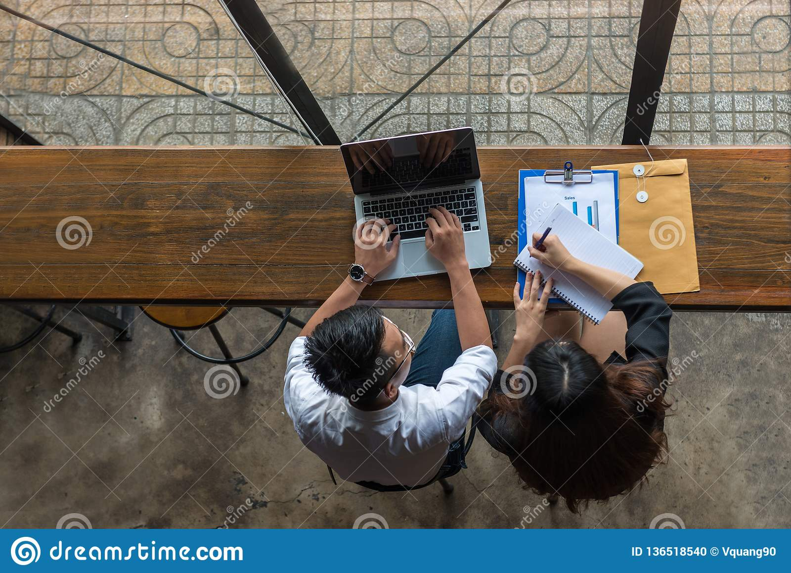 Businessman using laptop, businesswoman writing notes