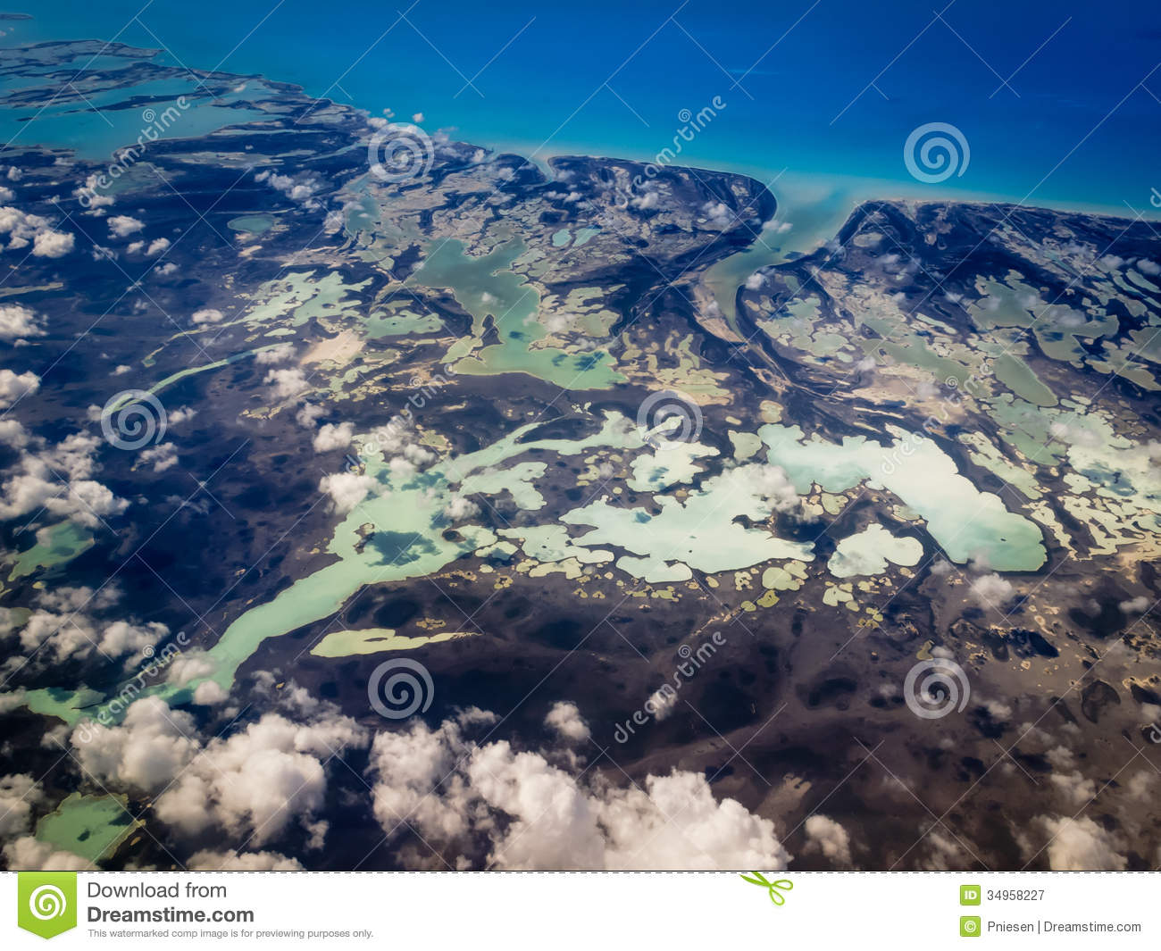 Aerial view of Caribbean various hues of greens and blues marbleized by land contours