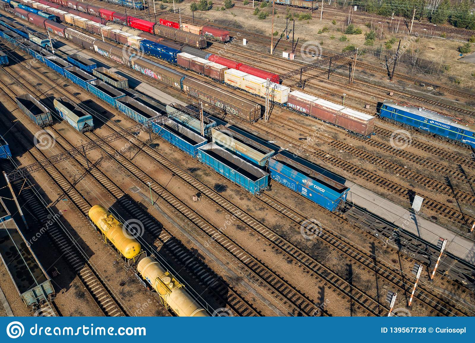 Aerial view of colorful freight trains on the railway station. Wagons with goods on railroad. Heavy industry. Industrial