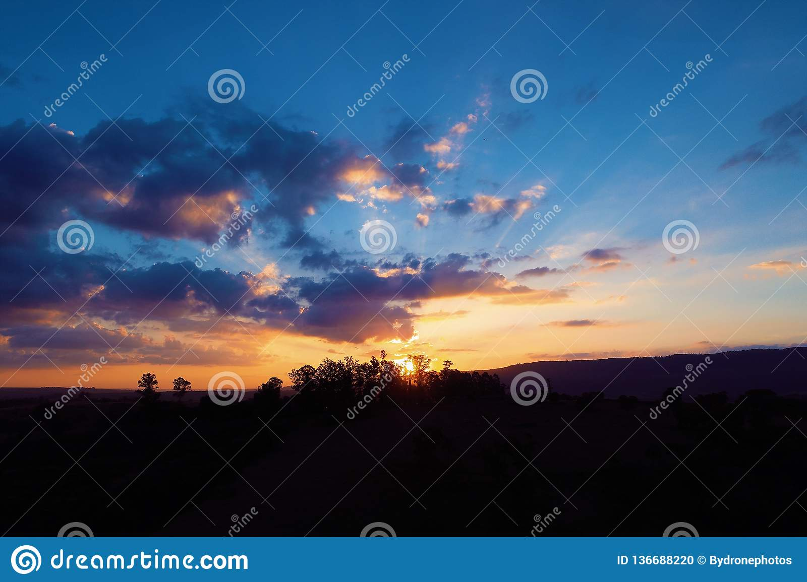 Aerial view of a countryside`s sunset with sunbeams from forest.