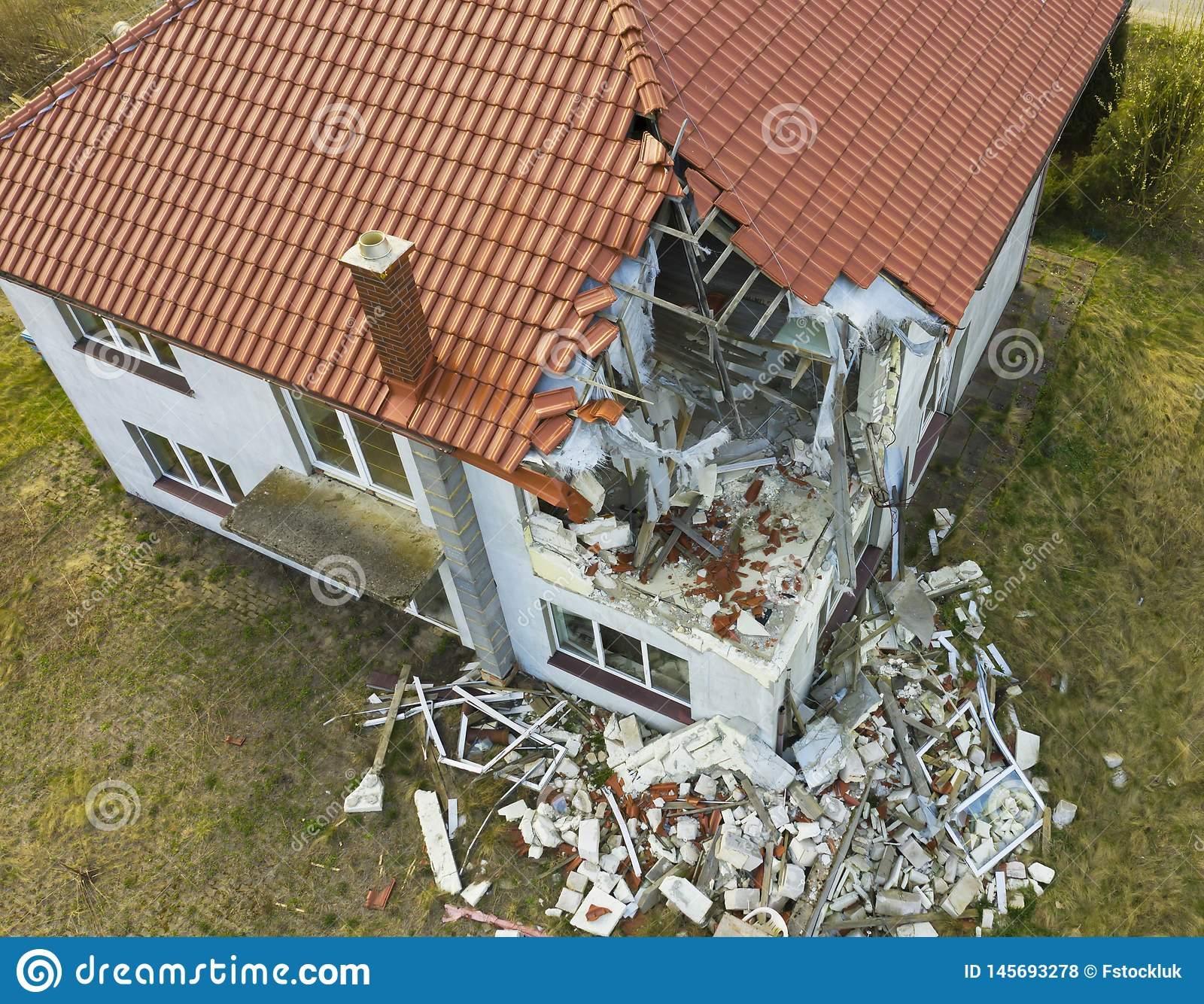 Aerial view on damaged red single house roof after strong wind or explosion. Hole in the rooftop and floor. Rubble on the ground