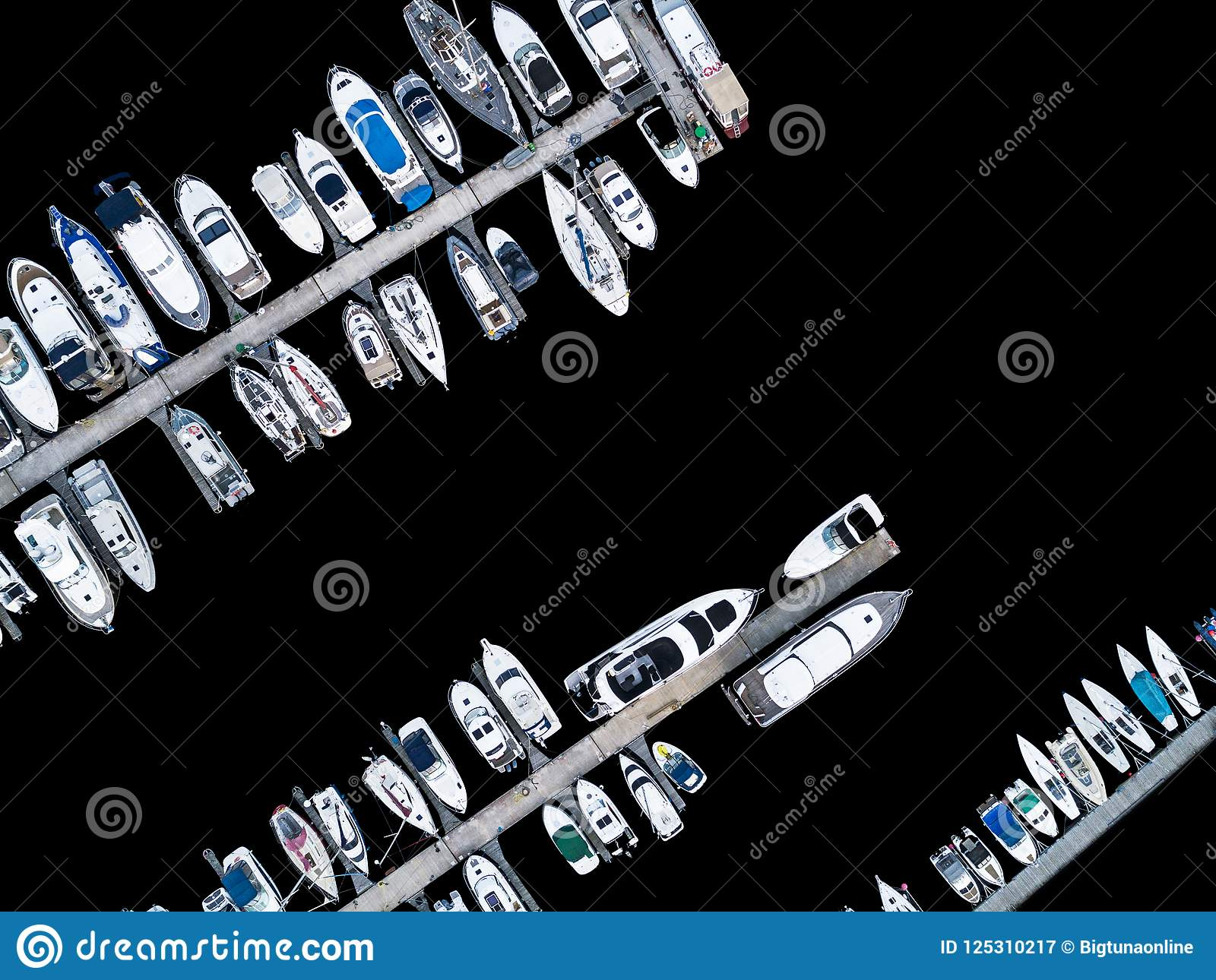 Aerial View by Drone of Yacht Club and Marina. Top view of yacht club. White boats in sea water. Marina dock yachts and small moto